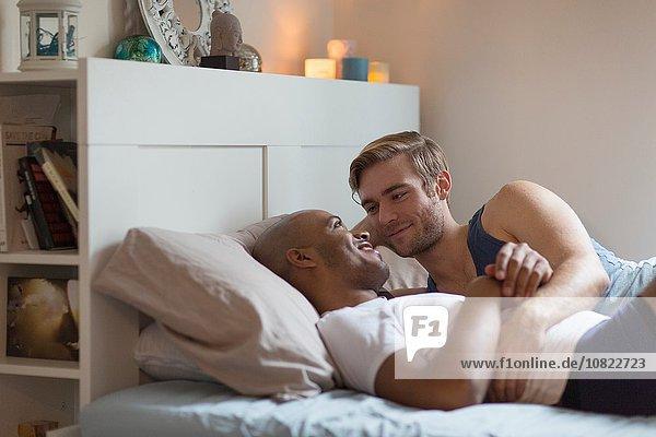 Männliches Paar im Bett liegend  von Angesicht zu Angesicht
