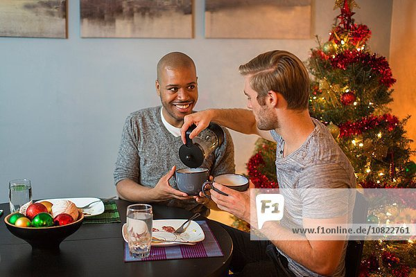 Male couple sitting at table  having breakfast together  Christmas tree in background