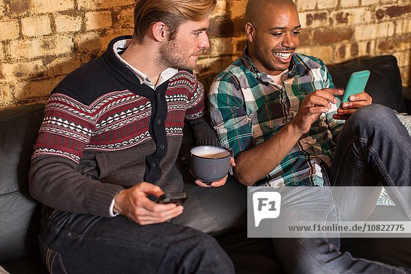 Male couple sitting on sofa  looking at smartphones