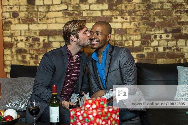 Männliches Paar sitzt auf Sofa  tauscht Weihnachtsgeschenke aus  junger Mann küsst Partner auf Wange