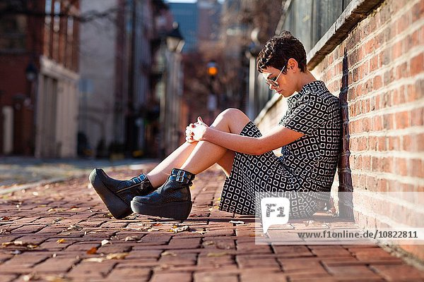 Mid adult woman sitting against brick wall