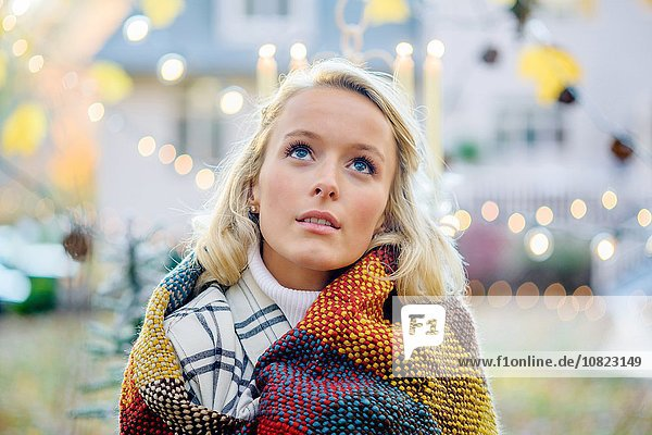 Portrait of young woman wrapped in blanket in front of xmas lights