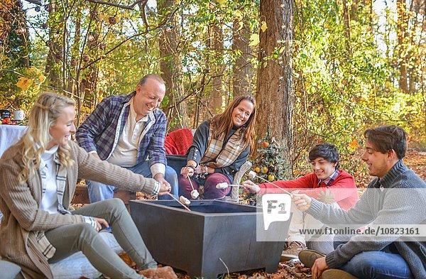 Eltern mit erwachsenen und jugendlichen Kindern rösten Marshmallows im Wald.