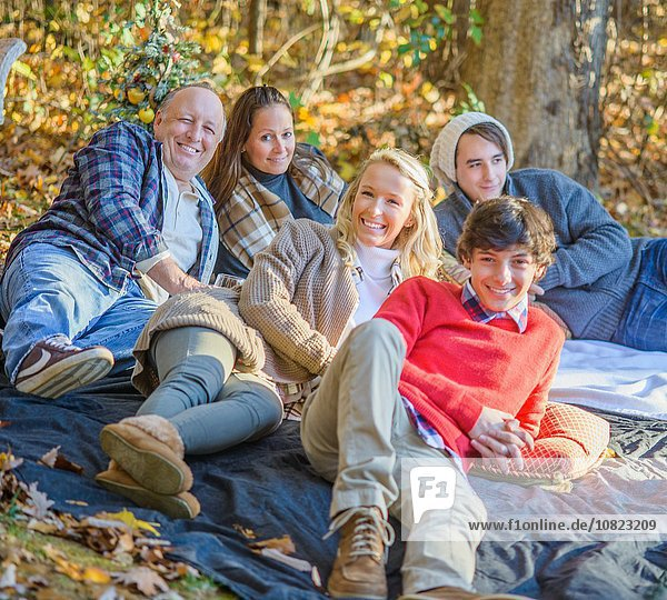 Portrait of mature couple with teenage and adult children relaxing on picnic blanket in woods