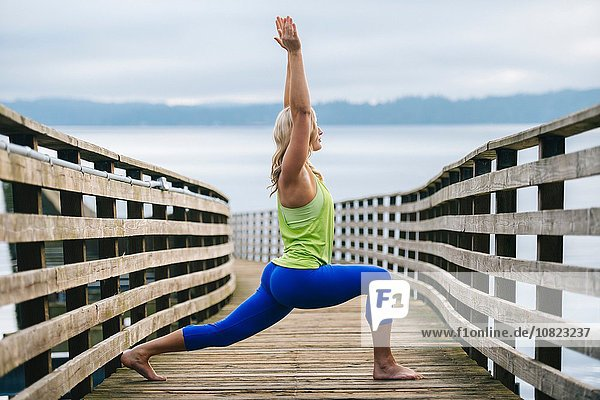 Portrait of young woman practicing yoga warrior pose on wooden pier