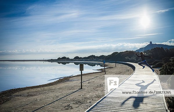 Junge Frau springt über Strandpromenade  Villasimius  Sardinien  Italien