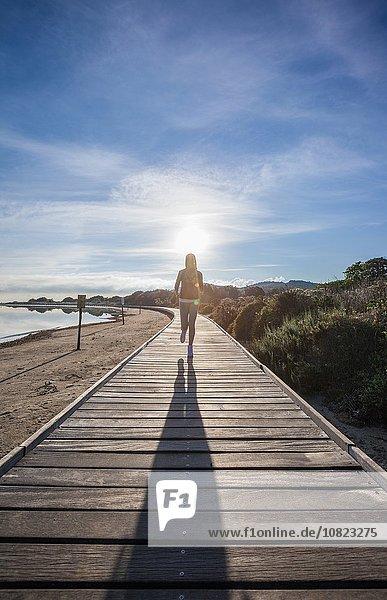 Läuferin und ihr Schatten entlang der Strandpromenade  Villasimius  Sardinien  Italien