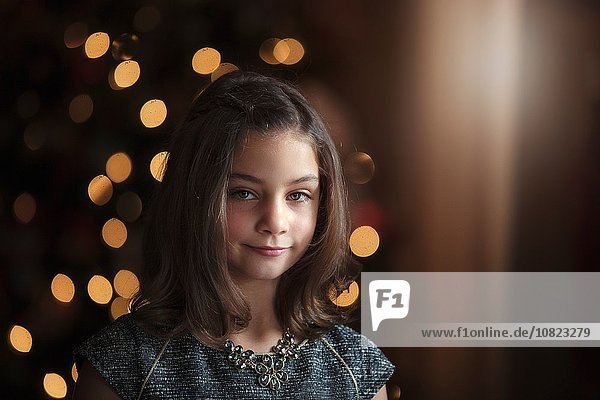 Portrait of girl in front of christmas tree looking at camera smiling