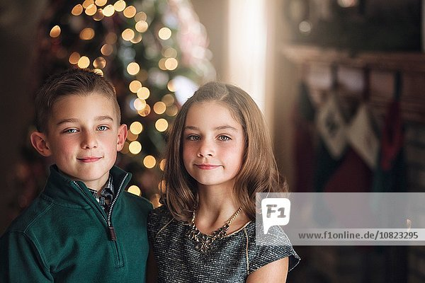 Portrait of girl and boy in front of christmas tree looking at camera smiling
