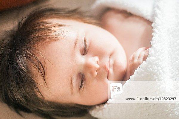 Hochwinkelansicht des schlafenden Mädchens in Decke gehüllt