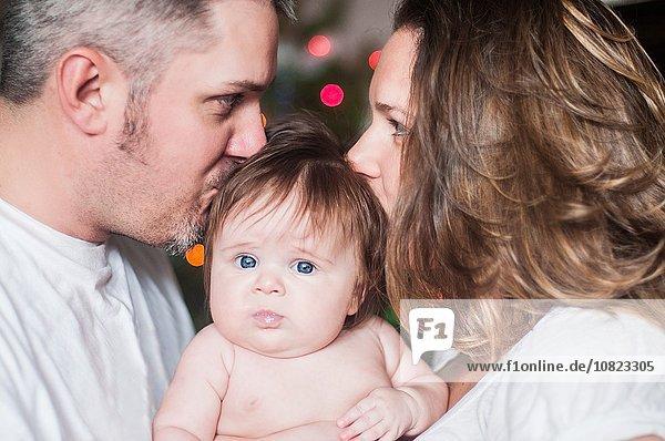 Mutter und Vater von Angesicht zu Angesicht haltendes kleines Mädchen,  das sich auf den Kopf küsst.