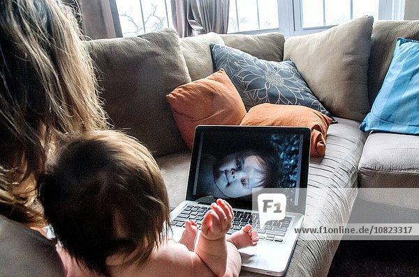 Über Schulteransicht der Mutter auf dem Sofa beim Betrachten von Fotos der Tochter auf dem Laptop