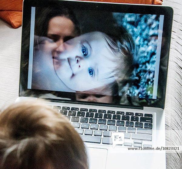 Spiegelung der Mutter beim Betrachten von Fotos der Tochter auf dem Laptop