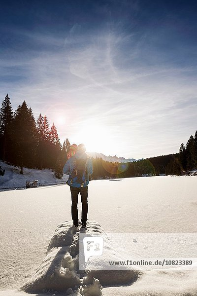 Rear view of man and toddler daughter looking out to snow covered lake  Berg  Bavaria  Germany