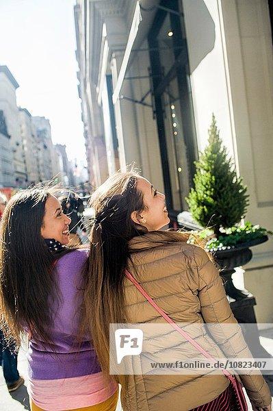 Rückansicht der jungen erwachsenen Zwillinge Schaufensterbummel in der Stadt