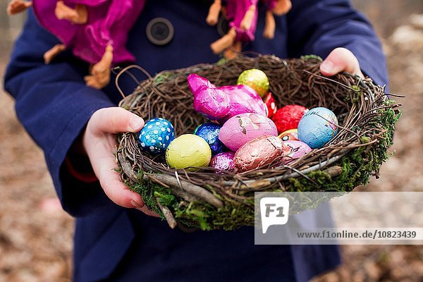 Cropped shot of female toddler holding basket nest of easter eggs in forest