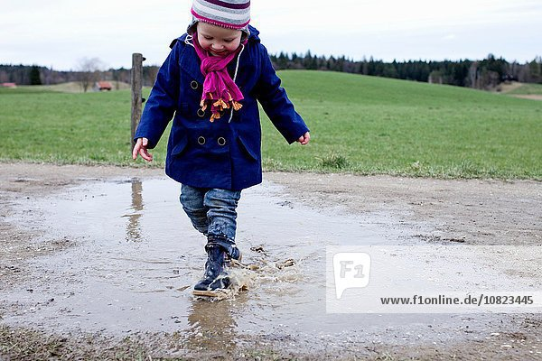 Female toddler wearing rubber boots splashing in puddle