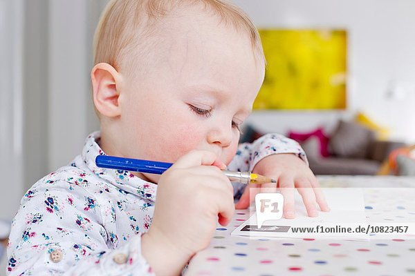 Female toddler drawing on paper at table