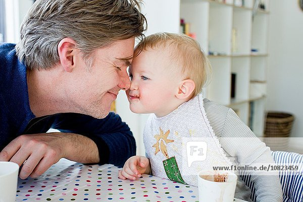 Female toddler and father face to face at kitchen table
