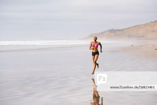 Frau im Bikini joggen am Strand
