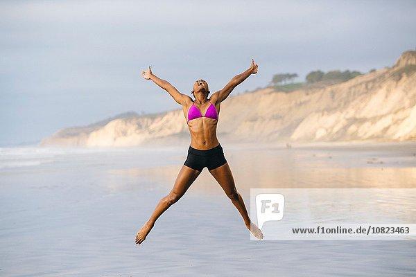 Frau im Bikini beim Springen am Strand