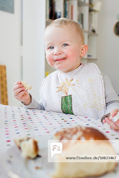 Female toddler eating bread at kitchen table