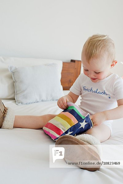 Female toddler playing with pencil case on bed