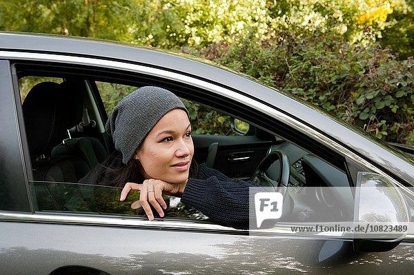Junge Frau  die sich lehnt und aus dem Autofenster schaut.