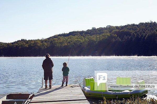 Children fishing on pier by lake  New Milford  Pennsylvania  US