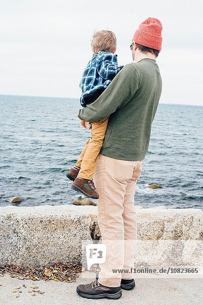 Father holding son beside lake  rear view