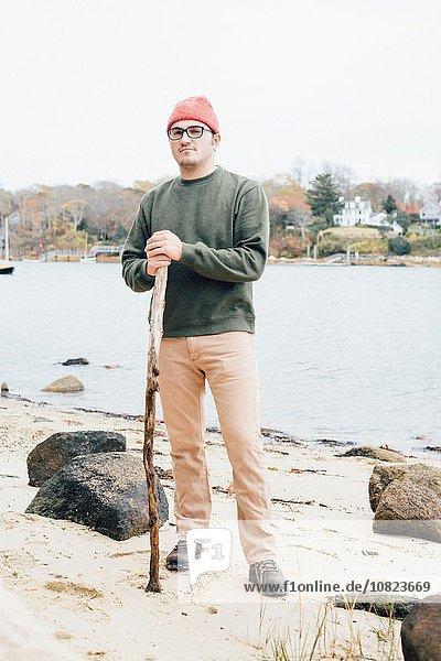 Porträt eines erwachsenen Mannes  der einen Spazierstock am See hält.
