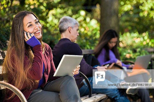 Junge Frau sitzt auf der Parkbank mit digitalem Tablett und chattet auf dem Smartphone.