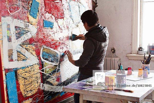 Male artist creating painted artwork