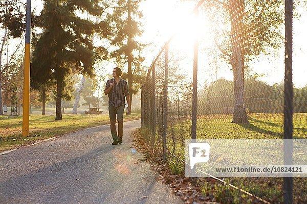 Vorderansicht des jungen Mannes  der auf dem Weg durch den Park spazieren geht.