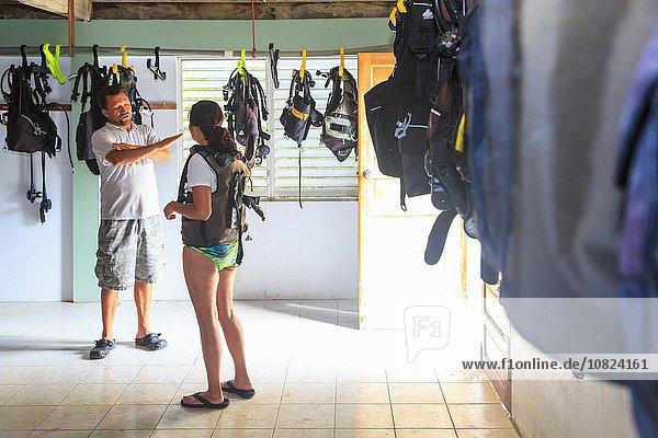 Tauchlehrerin  die weiblichen Touristen erklärt  St. Georges Caye  Belize  Zentralamerika