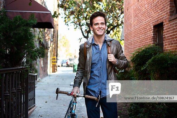 Glücklicher junger Mann schlendert mit Fahrrad auf dem Bürgersteig