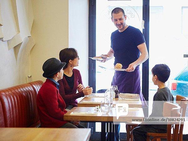 Kellner serviert Mittagessen im Restaurant für Frau und Söhne