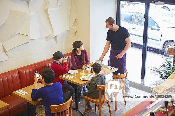 Kellner serviert Mittagessen im Restaurant für die Familie mit Jungen
