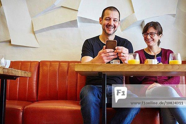 Mittleres erwachsenes Paar beim Lesen von Smartphone-Texten im Restaurant