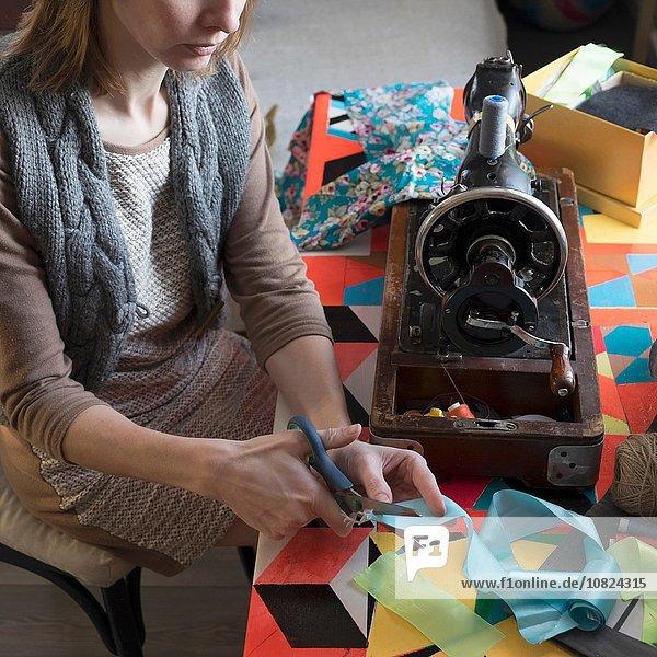 Frau mit Vintage-Nähmaschine schneidet Band am Tisch