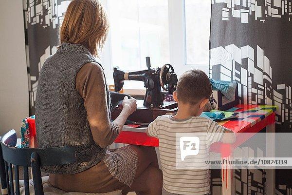 Frau und Kleinkind Sohn mit Vintage-Nähmaschine am Tisch vor dem Fenster