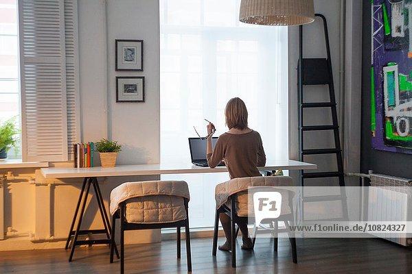 Rückansicht der mittleren erwachsenen Frau mit Laptop am Tisch vor dem Fenster