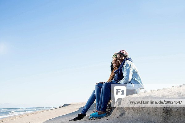 Two friends sitting on beach  looking at view