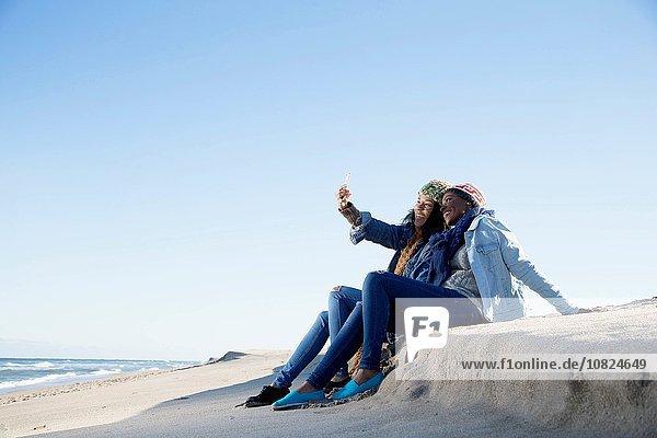 Two friends sitting on beach  taking self portrait  using smartphone