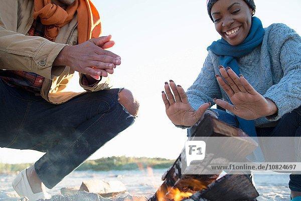 Friends warming hands over camp fire