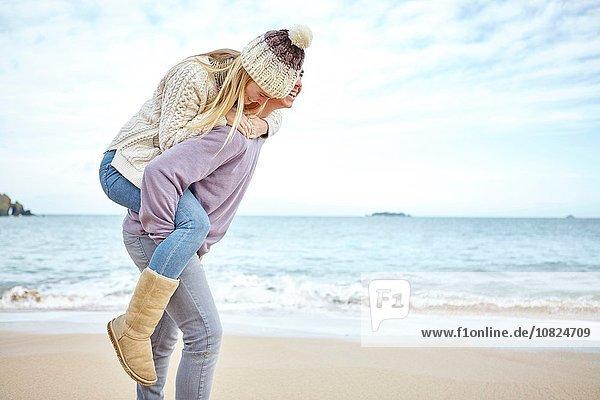 Junger Mann gibt Freundin ein Huckepack am Strand  Constantine Bay  Cornwall  UK Junger Mann gibt Freundin ein Huckepack am Strand, Constantine Bay, Cornwall, UK