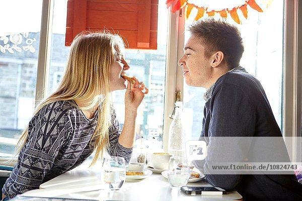 Romantisches junges Paar beim Mittagessen im Café-Fenstersitz