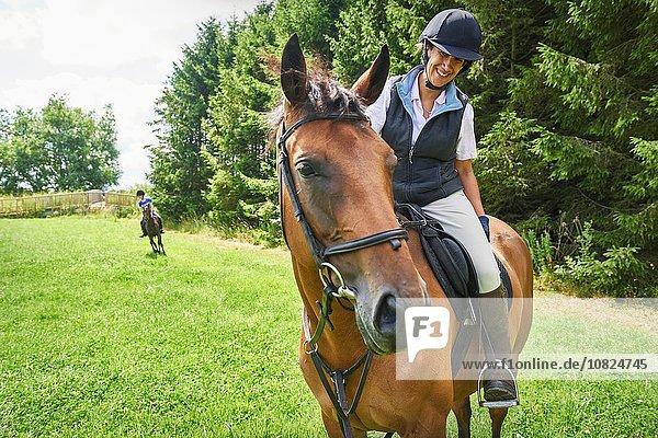 Reife Frau auf dem Rücken eines Pferdes mit Reitkappe und Stiefeln beim Anblick eines lächelnden Pferdes.