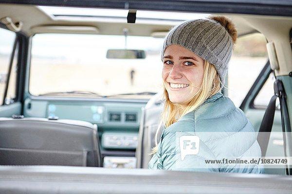Porträt einer jungen Frau im Auto am Strand mit Strickmütze