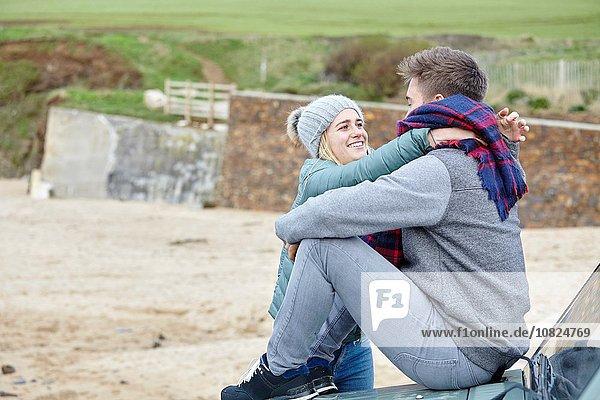 Romantisches junges Paar auf einer Motorhaube am Strand sitzend